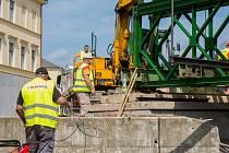 Dělníci připravují mostní provizorium přes říčku Čistou, po kterém budou jezdit auta během opravy památkově chráněného mostu v centru Hostinného.
