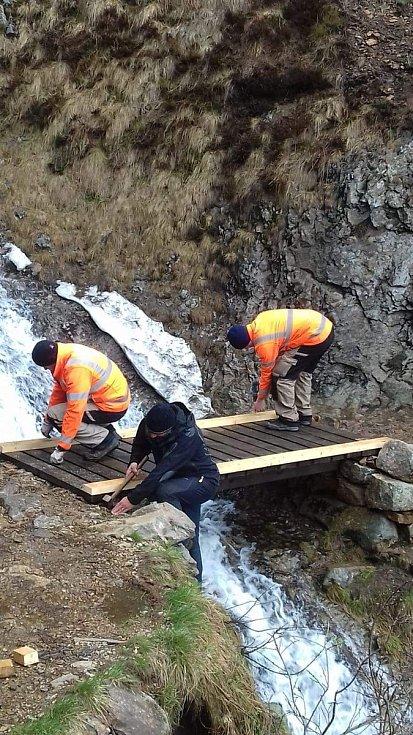 Pracovníci Technických služeb Pece pod Sněžkou ve čtvrtek opravili dřevěnou lávku u Trkače v Rudné rokli, která vede přes Rudný potok.