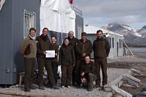 Skupina pracovníků Správy KRNAP před polární stanicí Josefa Svobody v zálivu Petunia.