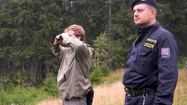 MONITORING LOKALITY. Dalekohled je nezbytnou součástí práce terénních pracovníků Správy KRNAP.  Na snímku obhlíží borůvkové svahy za  asistence policisty Libor Janda .