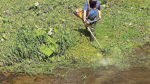 Sekání trávy v řece Úpě v Trutnově.