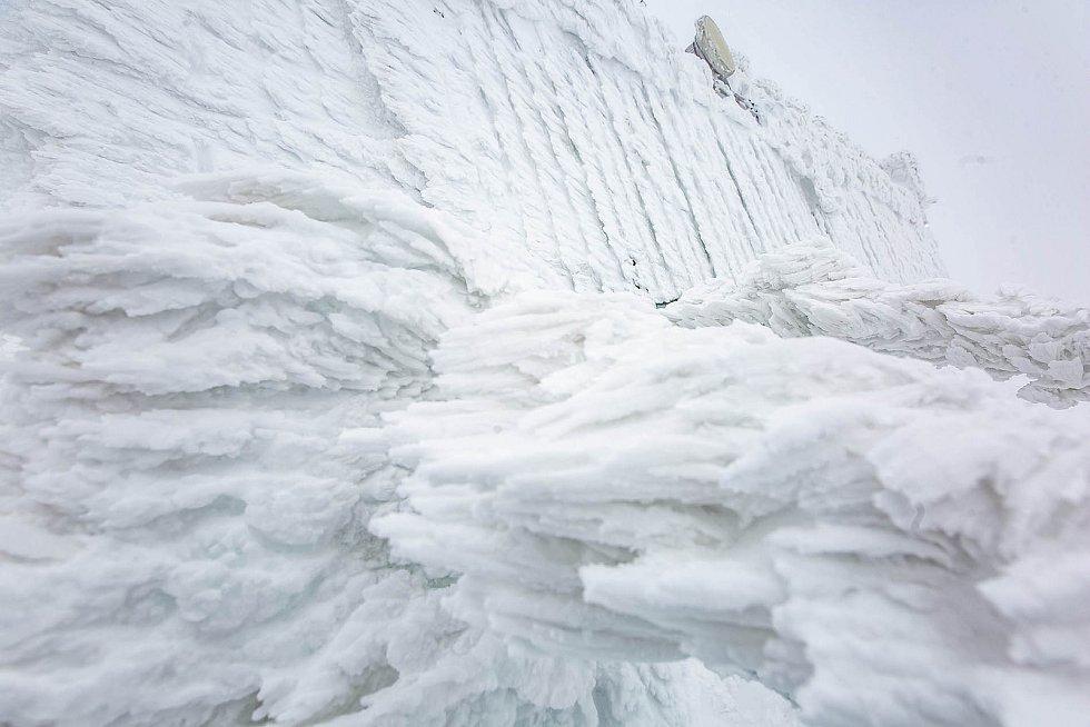 Království sněhu. Česká Poštovna Anežka na Sněžce je zasypaná sněhem. Zaměstnancům trvalo několik hodin, než se vůbec prokopali ke vstupním dveřím. Postupně jim pomáhají dobrovolníci, stejně jako v pátek Tomáš Řezníček z Lázní Bohdaneč a Kateřina.