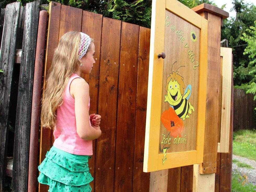 PŘÍRODNÍ DÍLNA. V proskleném úlu u domu Miloše Davida se mohou děti i dospělí přiučit, jak pracují včely. Šest pláství je tu schováno za dřevěnými dvířky, které jdou lehce otevřít.