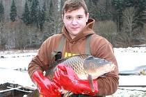 TO JE MACEK! Jeden z trutnovských rybářů Lukáš Saibert s devítikilovým kaprem v petříkovických sádkách.