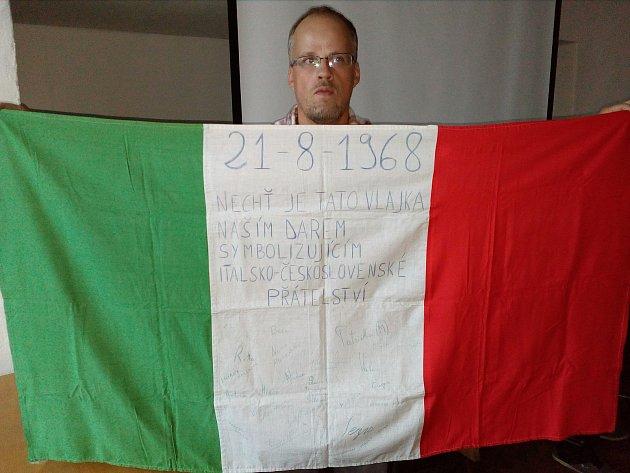 Italský prapor s datem 21.8.1968, nápisem Nechť je tato vlajka naším darem symbolizujícím italsko-československé přátelství a třiceti podpisy.