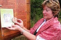 MALOÚPSKÝ GROŠ získají účastníci pohádkové stezky v Malé Úpě, kteří budou mít omalované všechny plastické ornamenty v knížečce. Na snímu groš a dokument ukazuje Marie Holomíčková.