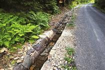 OPRAVENÁ CESTA a ručně vyskládaný vzorový kamenný příkop odolává dešťům.