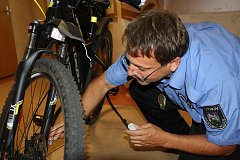 Jan Bábik, koordinátor prevence kriminality Městské policie Trutnov, při značení elektrokola syntetickou DNA.