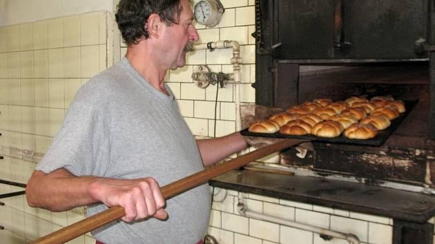 PEKAŘ MILOŠ KAZDA vytahuje plech s houskami z pece, která je  z roku 1976. Teplota na pečení je kolem 230 stupňů.  Pečivo uvnitř se musí hlídat pohledem,  pec nepeče rovnoměrně.