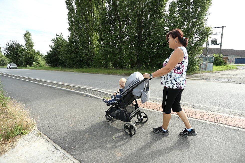 Církvice na Kutnohorsku. Žena s kočárkem poblíž areálu firmy, ve které se rozšířila nemoc COVID-19