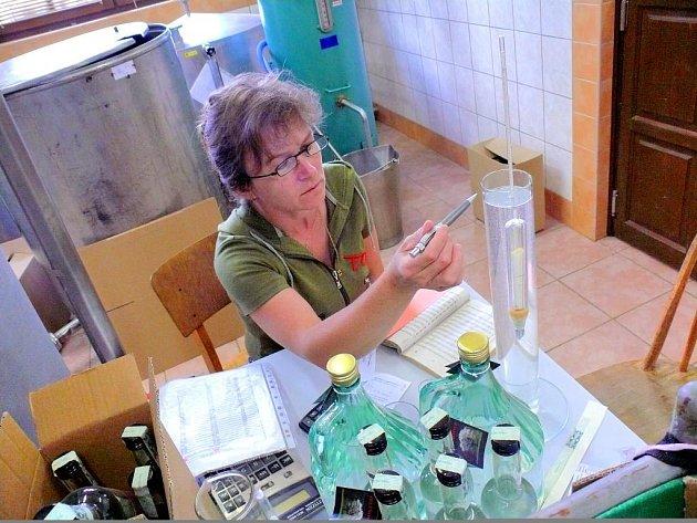 Zaměstnankyně palírny kontroluje kvalitu alkoholu.