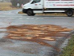 Stopa na silnici po dopravní nehodě na křižovatce Na Markétě u Suchdola.