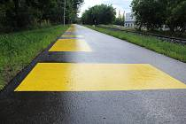 Žluté vodorovné značení na cyklostezce podél říčky Vrchlice v Kutné Hoře.