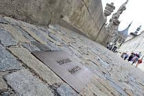 Označení soch bronzovou deskou před bývalou jezuitskou kolejí v Kutné Hoře.