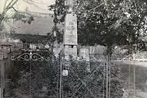 Pomník padlých v Malenovicích, za ním křížek v horní části návsi.