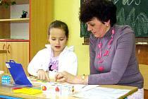 Ilustrační foto: Dominika Karlová ukazuje znalosti písmen, což kontroluje paní učitelka Olga Ladrová.