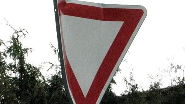 Zohýbaná značka Dej přednost v jízdě u čerpací stanice KM-Prona.