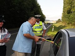 Policisté komunikují s dětmi, které jsou spolujezdci ve vozidlech.