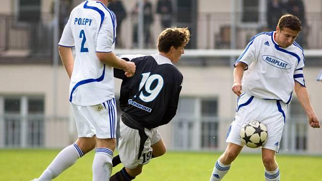 Čáslavský Aleš Urban (číslo 19) sleduje počínání polepského středopolaře Lukáše Kmocha v zápase, který skončil bez branek. Situaci ještě sleduje hostující obránce Týma (vlevo)