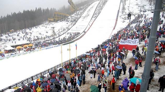 ZAPLNĚNÉ HLEDIŠTĚ ZŮSTANE LETOS ASI SNEM. Takto se scházeli příznivci lyžování do harrachovského areálu v lednu 2008. Tehdy se odskákalo alespoň jedno kolo Světového poháru. Letos to vypadá, že hlediště zůstane opuštěné.