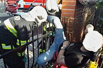 Hasiči pomáhají muži, který se při přelézání plotu v Liberci - Vratislavicích nohou nabodl na mříž