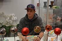 """SKLÁŘ JAKUB. Návštěvníkům předváděl, jak se vyrábějí vánoční ozdoby, také student 3. ročníku oboru Sklář Jakub Kroutil. """"Není to jen obyčejné řemeslo, je to umění,"""" říká."""