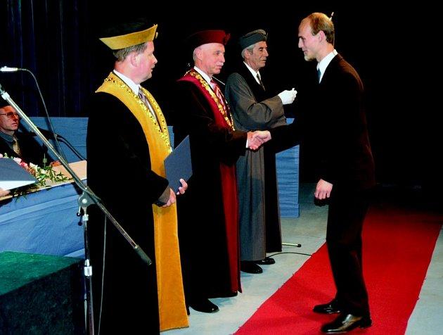 Absolvent fakulty Michal Frolík přijímá od rektora univerzity Vojtěcha Konopy gratulace k bakalářskému titulu.