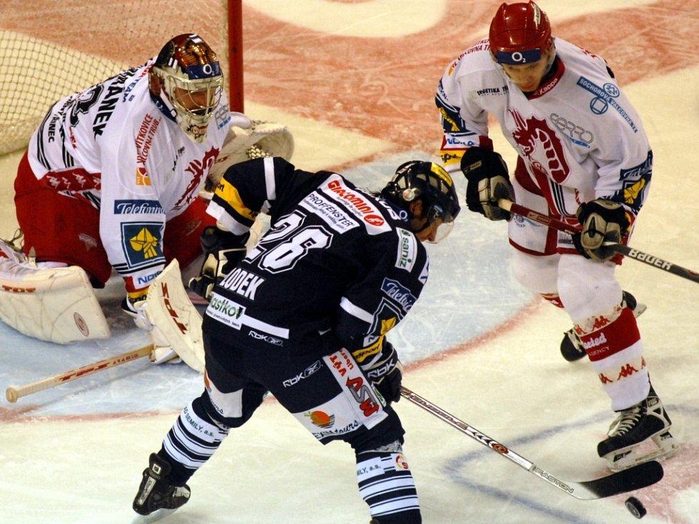 Z TOHOTO GÓL JEŠTĚ  NEBYL. . Liberecký hokejový útočník J. Plodek se ocitl v této situaci v dobré pozici před třineckým brankářem R. Čechmánkem. Tentokrát gól ještě nedal, ale úspěšnou trefou na 2:1 si to vynahradil. Vpravo třinecký obránce J. Andersons.