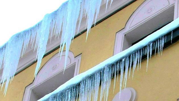 NEBEZPEČÍ představují v zimních ulicích rampouchy. Zatímco s úklidem sněhu si už město alespoň na páteřních komunikacích a chodnících vcelku poradilo, chodce teď ohrožuje  led na střechách.