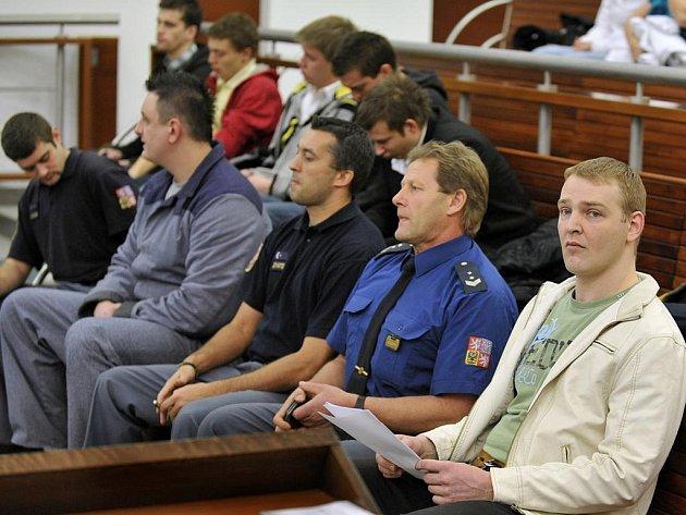 ZAPLNĚNÁ JEDNACÍ SÍŇ. Devět obžalovaných, devět obhájců, členové vězeňské služby.