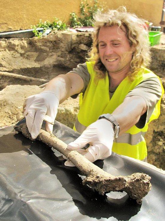 Terénní technik Antonín Gábr vyzvedává stehenní kost mrtvého vojáka z hromadného hrobu. Po 254 letech se tak nejspíše rakouský voják dostává na povrch.