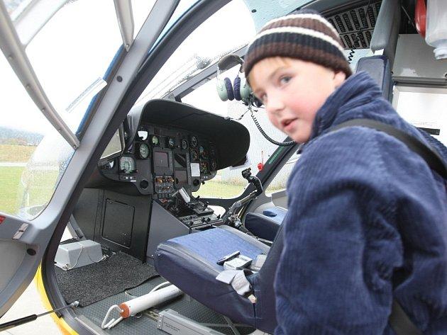 Děti na návštěvě u letecké záchranné služby na letišti v Liberci. Kabinu pilota vrtulníku si prohlíží Jakub Kříž.