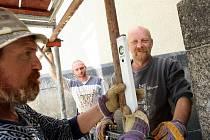 Dělníci staví lešení pro řemeslníky na pravé straně kostela svatého Antonína v Liberci.