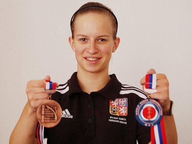 Devatenáctiletá karatistka s medailemi.