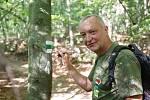 Jaromír Růžička z Klubu českých turistů obnovuje turistickou značku na kmenu stromu.