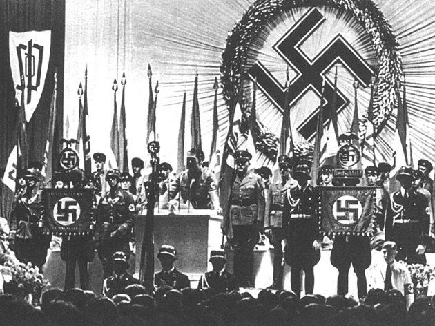 Hitlerův náměstek Rudolf Hess přijímá na libereckém výstavišti vlajku od Konrada Henleina.