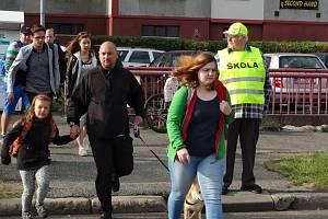 Senioři dohlížející na přechody u škol.