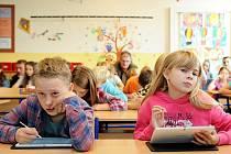 """TABLETY v hodině děti baví. Během ukázkové hodiny je páťáci využívali jako záznamový list na diktát německých číslic, jako podklad k vypočítání matematické úlohy a nakonec jako """"papír"""", na kterém odpoví na otázku zobrazenou na interaktivní tabuli."""