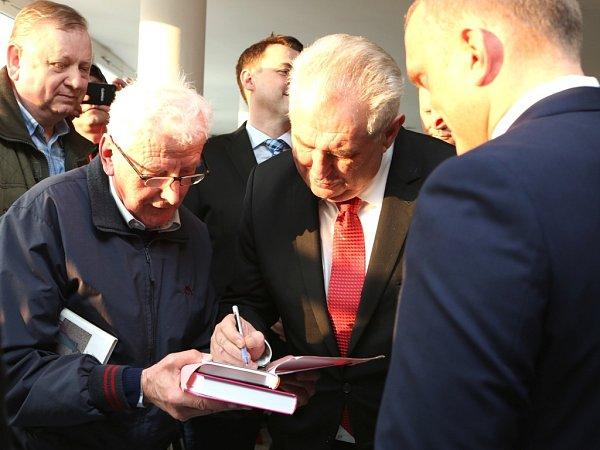 Miloš Zeman se podepisuje do památníčku svým fanouškům.