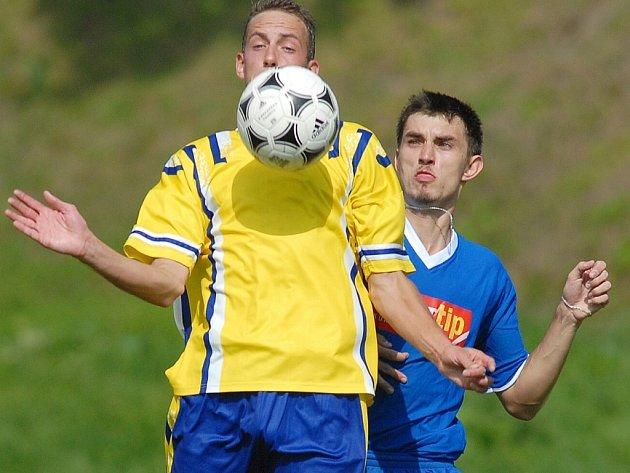 FOTBAL U VOJÁKŮ. Obránce si zpracovává míč.