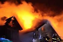 Střechu domu pohltily plameny.
