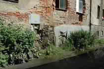 Jímka v suterénu jednoho z domů, jehož stěnou prosakuje odpadní voda ven.