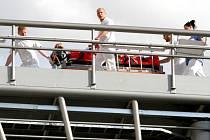 ZRANĚNÉHO MUŽE převáží ve speciálním vozíku personál nemocnice od vrtulníku na heliportu umístěném na trojnožce až do nemocniční budovy.