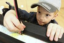 Děti zkoušejí v knihovně, co všechno se dá dělat s papírem.