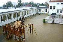 Rozvodněná Ploučnice hrozivě zaplavila na konci týdne zahradu místní mateřské školky.