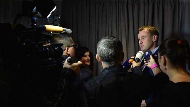 Martin Půta je obklopen novináři.