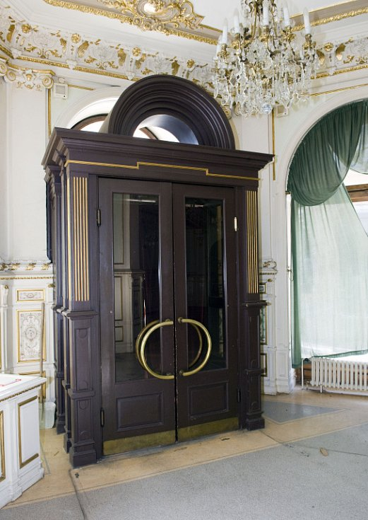 Interiér kavárny Pošta. Vstupní dveře zevnitř.