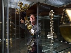 Kurátor výstavy Miroslav Cogan instaluje procesní kříž.