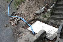 HADICE SE TÁHNE ODNĚKUD ZE SKLEPA. Hadice se vine ze sklepních prostor domu až do kanálu na silnici.