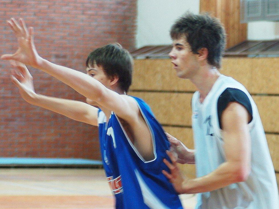 Více jak dvoumetrový (209 cm) basketbalista Slavie TU Jan Smeták (v bílém) brání soupeře.